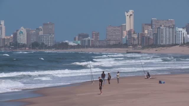 ws fishermen on beach in front of durban skyline / durban, south africa - 男漁師点の映像素材/bロール