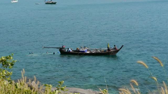 fishermen on boat in thailand. - spoonfilm stock-videos und b-roll-filmmaterial