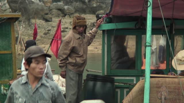 vidéos et rushes de ms pan fishermen on docked boat, halong bay, vietnam - cadrage aux genoux