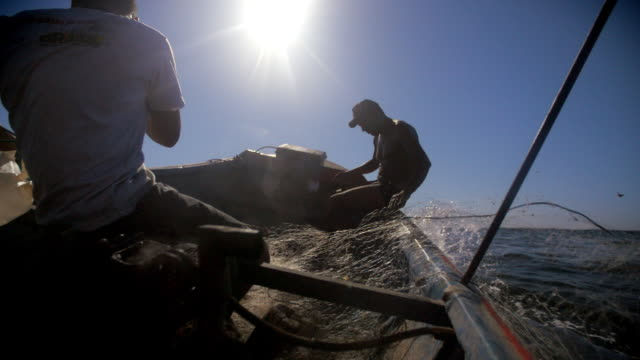 fishermen on motorboat cast fishing net into the sea in slow motion, splashing camera with ocean spray - cast member stock videos & royalty-free footage