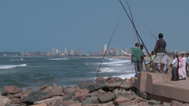 ws fishermen on pier by the ocean next to durban skyline / durban, south africa - 男漁師点の映像素材/bロール
