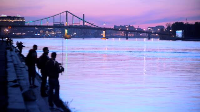 vídeos de stock, filmes e b-roll de os pescadores no banco do rio, à noite - brightly lit