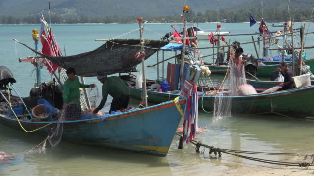 fishermen pull in the net on fishing boats moored on beach - ko samui stock videos & royalty-free footage