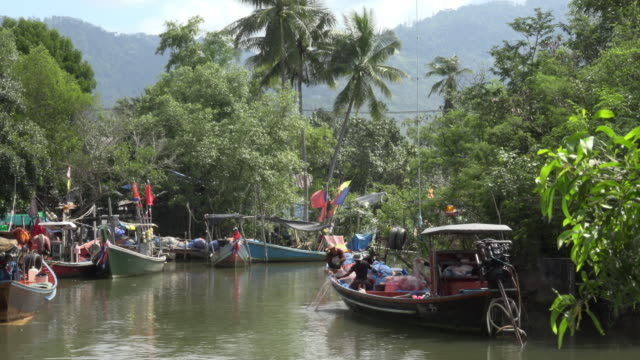 Fishermen pull in the net on fishing boats moored on river at fishing village