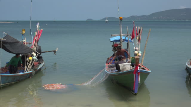 Fishermen pull in the net on fishing boats