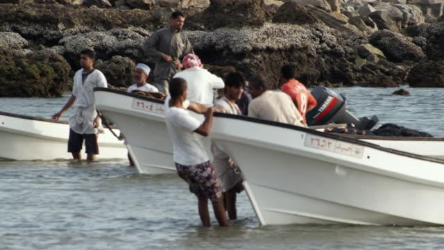 ms pan fishermen pulling boat through shallow water / sur, oman  - hand an der hüfte stock-videos und b-roll-filmmaterial