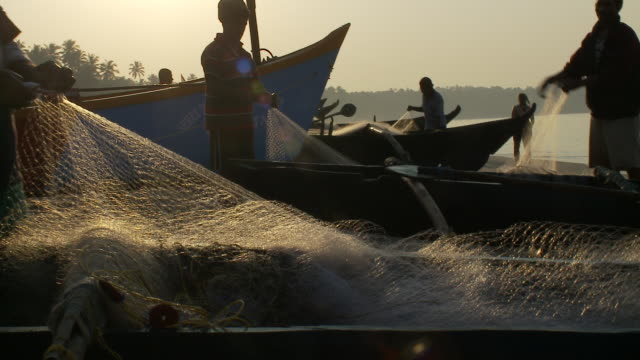 fishermen remove small fish from a fishing net on palolem beach in the golden hour. - indian ocean stock videos & royalty-free footage