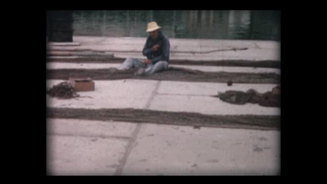 vídeos y material grabado en eventos de stock de 1963 fishermen repair nets quayside - color tipo de imagen