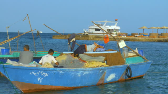 ws pan fishermen sitting and sleeping in boat at red sea bay / hurghada, red sea coast, egypt - hurghada stock-videos und b-roll-filmmaterial