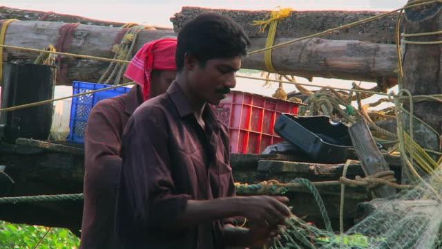 MS Fishermen tending to nets / Anjuna, Goa, India