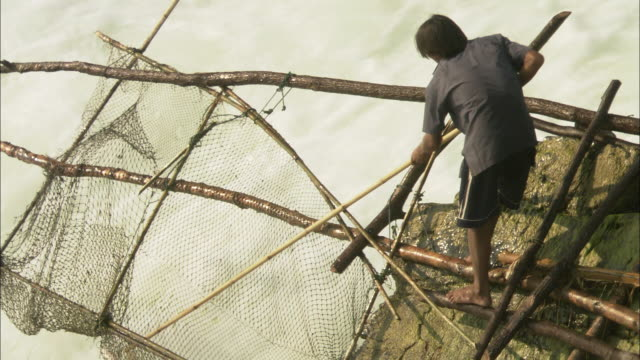 a fishermen traps fish in a net at the base of a powerful waterfall on the mekong river. - recreational pursuit stock videos & royalty-free footage