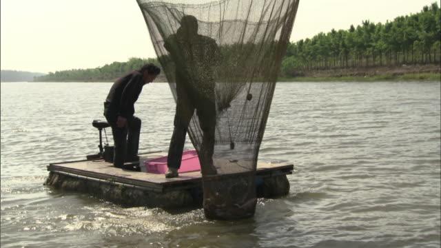 vídeos de stock e filmes b-roll de fishermen using a mechanical net, china - rede de pesca comercial