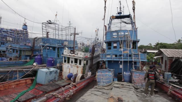 Fishermen wait to clear their documents at Songkhla port in Songkhla Thailand on Wednesday Dec 23 Fishing boats sit docked at Songkhla port in...