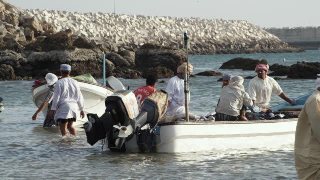 ms fishermen with boats in shallow water / sur, oman  - 頭飾り点の映像素材/bロール