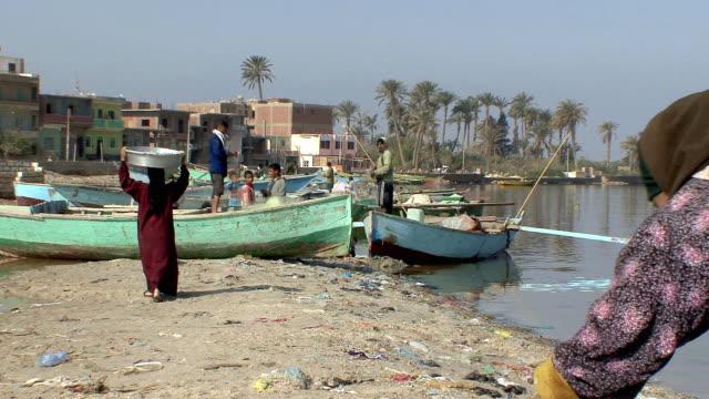 vídeos de stock, filmes e b-roll de ws fishermen working at boats on shores of qarun lake in fayoum region, qarun, egypt - egito