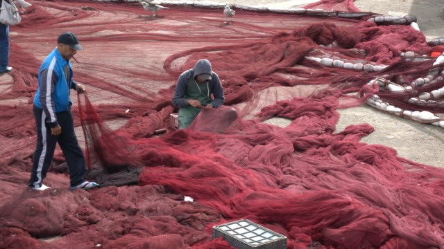 fishermen working on their fishing nets at the port of essaouira in morocco - effort video stock e b–roll
