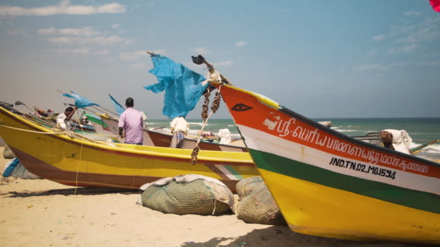 fishermen working with the net next to boats at beach of chennai, tamil nadu, india - chennai stock videos & royalty-free footage