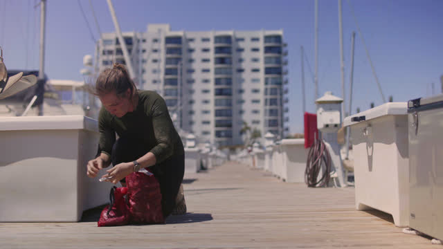 fisherwoman attaches tags to a red bag filled with fresh mussels to prepare for delivery to commercial kitchens. - ミヤコドリ点の映像素材/bロール