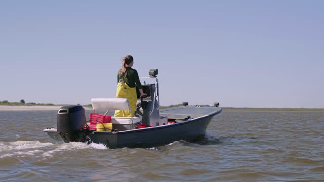 fisherwoman drives boat in the intracoastal waterway to harvest oysters in oyster beds nearby - incentive stock videos & royalty-free footage