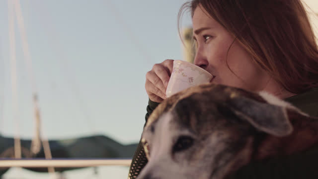 fisherwoman pours coffee into a coffee cup and takes a sip while petting her dog on the deck of a docked yacht in a marina - fischerboot stock-videos und b-roll-filmmaterial