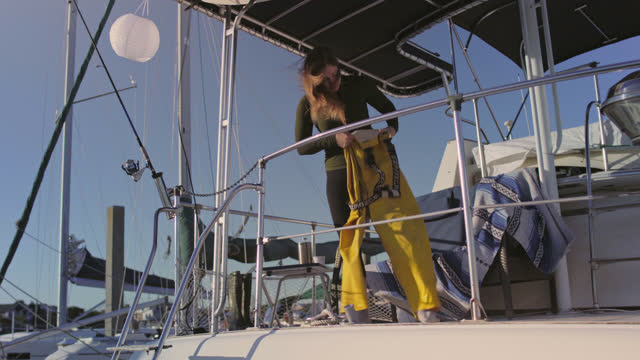 fisherwoman puts on waders on the deck of a docked yacht after a coffee break in a marina and then gives her a dog a hug and kiss - incentive stock videos & royalty-free footage