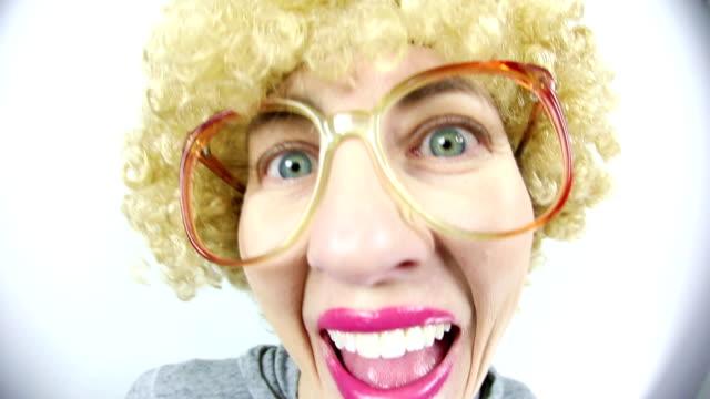 金髪アフロのかつらを持つ魚眼レンズ幸せオタク - 中年の女性点の映像素材/bロール