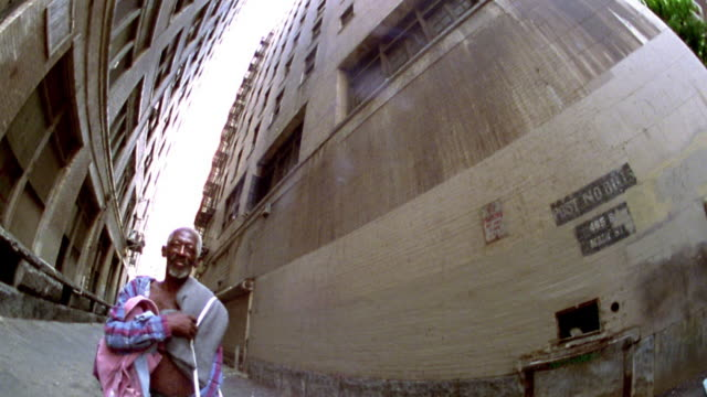 Fisheye tilt down mature Black man in open shirt (homeless) in alley between skyscrapers / Los Angeles