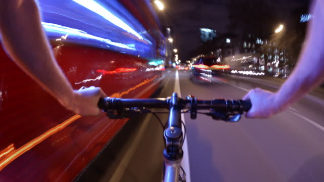 a fisheye pov view of a cyclist nighttime journey travelling rapidly down the euston road in central london - cycling stock videos and b-roll footage