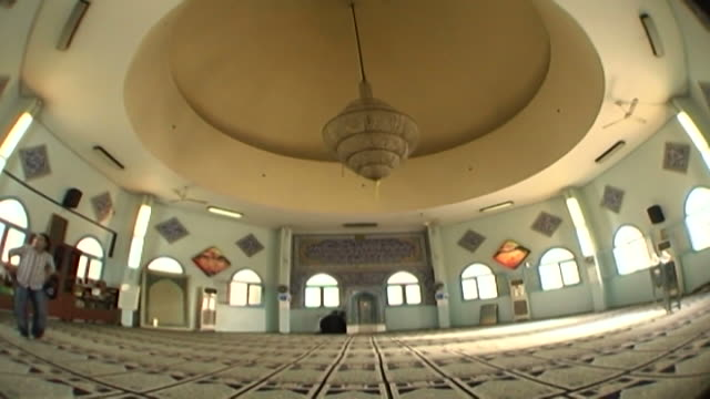 fisheye view of a shia cleric kneeling at the mihrab of the chatila mosque which is decorated in ceramic tiles covered in qoranic verses and foliate... - shi'ite islam stock videos & royalty-free footage