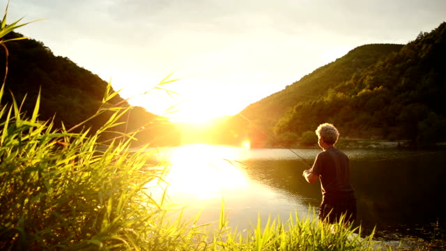 fishing at sunset - fishing rod stock videos & royalty-free footage