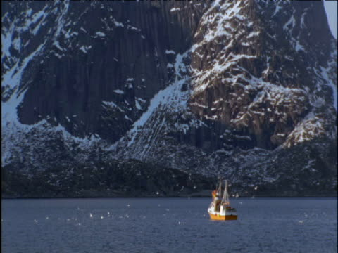 fishing boat and gulls in mountain lined fjord - traditionally norwegian stock videos & royalty-free footage