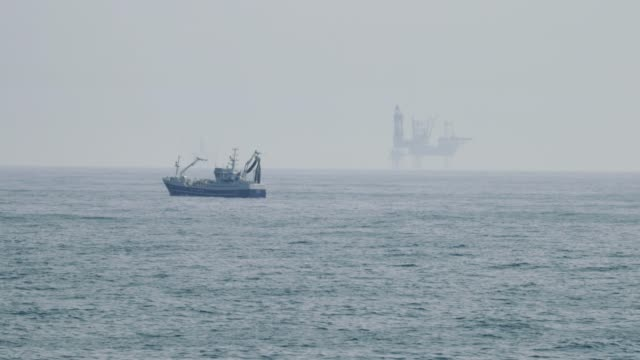 fishing boat and oil platform in north sea - motor oil stock videos and b-roll footage