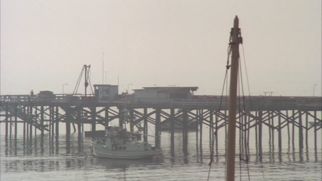 WS, PAN, Fishing boat at pier and small beach house, Malibu, California, USA