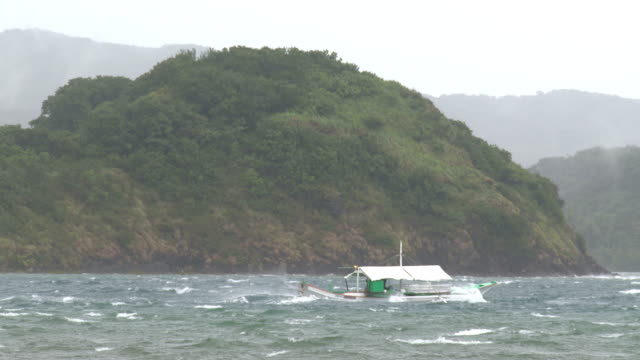 a fishing boat braves rough seas as typhoon noul nears northern philippines on 10th may 2015 - atlanta braves stock-videos und b-roll-filmmaterial