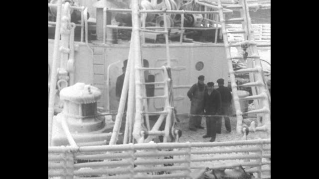 fishing boat caked in ice motors into port past ship encased in ice at dock / tug boat pushes ocean liner covered with ice through port / vs crew on... - 1930 stock-videos und b-roll-filmmaterial