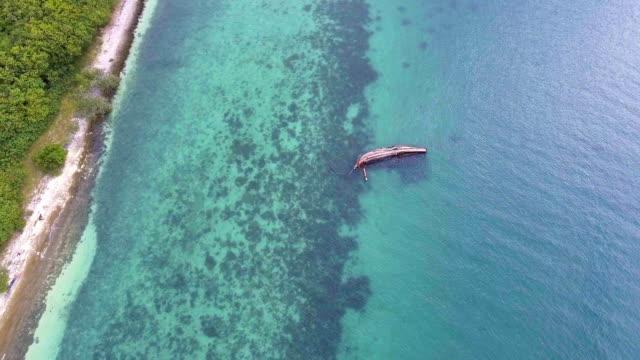 stockvideo's en b-roll-footage met vissersboot kapseizen in de zee met drone. - scheepswrak