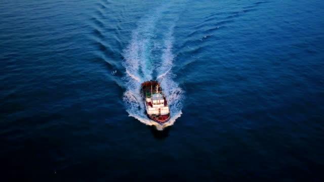 vídeos de stock e filmes b-roll de fishing boat coming back to the harbor - navio pesqueiro