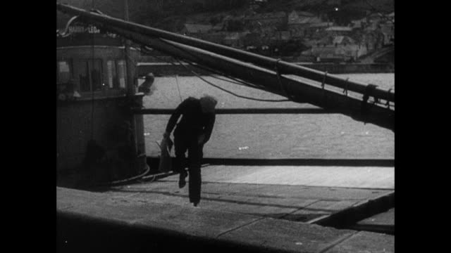 b/w fishing boat coming into harbor a man getting off boat and walking along dock with another man talking to him / cornwall, england, united kingdom - bay of water stock videos & royalty-free footage
