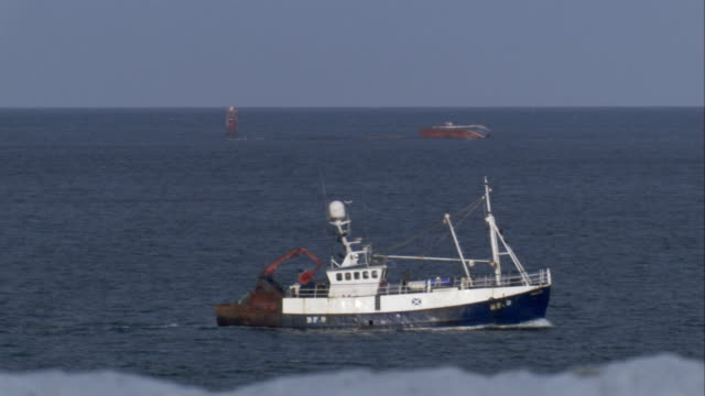 a fishing boat cruises through the water off the coast of scotland. available in hd. - クロヴィー点の映像素材/bロール