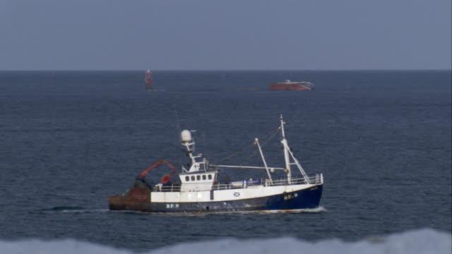 vídeos de stock, filmes e b-roll de a fishing boat cruises through the waters of the north sea. available in hd. - boia equipamento marítimo de segurança