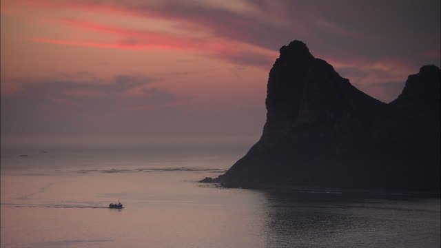 a fishing boat cruises towards cape peninsula at golden hour. - standbildaufnahme stock-videos und b-roll-filmmaterial