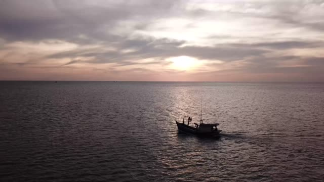 a fishing boat cruising on the sea of phu quoc island, vietnam at sunset - 4k aerial video - vietnam meridionale video stock e b–roll