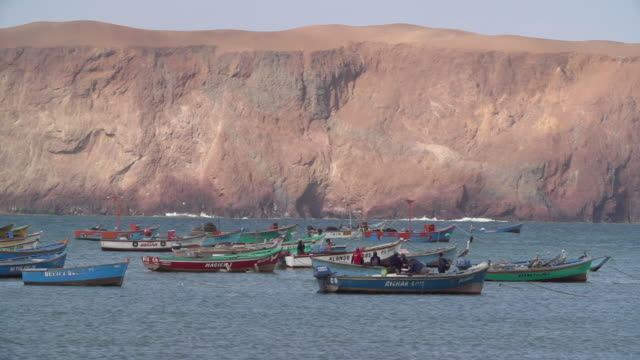 fishing boat drives through flock of empty boats - peruvian ethnicity stock videos and b-roll footage