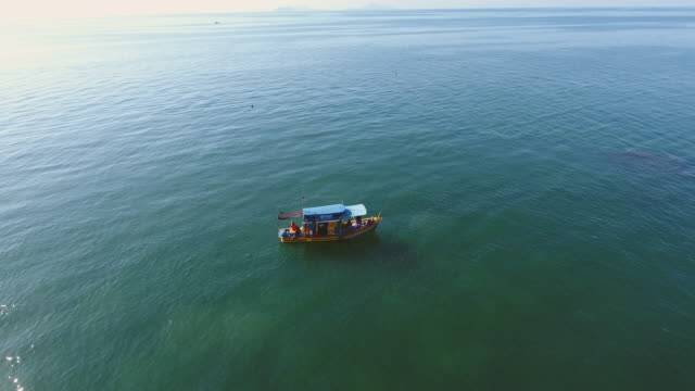 fishing boat in a sea with transparent water, aerial video - south east asia stock videos & royalty-free footage