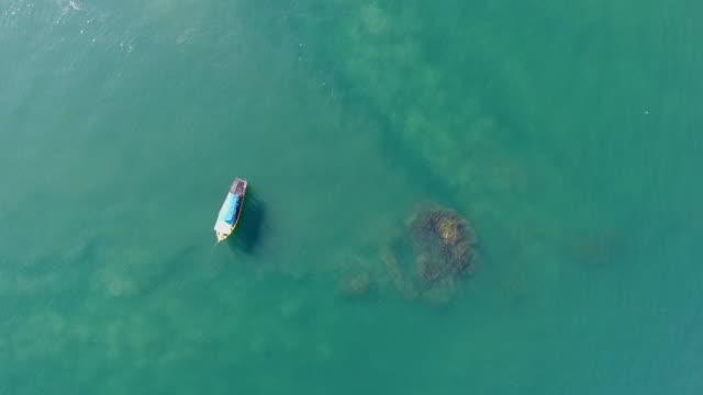 fischerboot in einem meer mit transparentem wasser, luftvideo - kleines wasserfahrzeug stock-videos und b-roll-filmmaterial