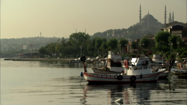 a fishing boat moors in a harbor. - istanbul stock videos & royalty-free footage