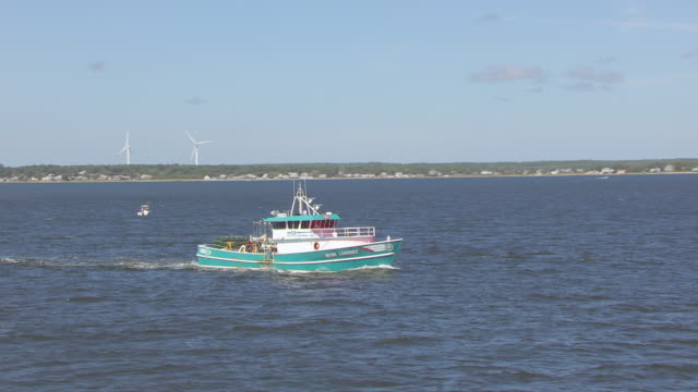 vidéos et rushes de ws zi aerial pov fishing boat moving in sea with city in background / new bedford, massachusetts, united states - industrie de la pêche