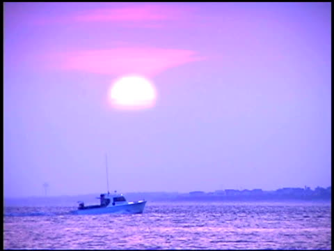 fishing boat on sea at sunset - bald head island stock videos and b-roll footage