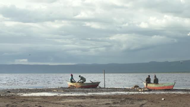 fishing boat on shoreline tableau at lake eyasi - medium group of animals stock videos & royalty-free footage