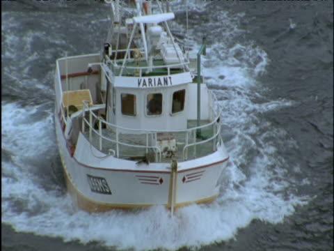 stockvideo's en b-roll-footage met fishing boat passes under camera on choppy sea - ruw